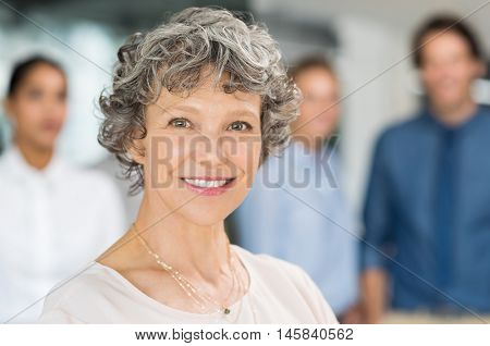 Senior businesswoman smiling and standing in front of a group of businesspeople. Portrait of a smiling business woman looking at camera. Close up of mature businesswoman with happy colleagues.