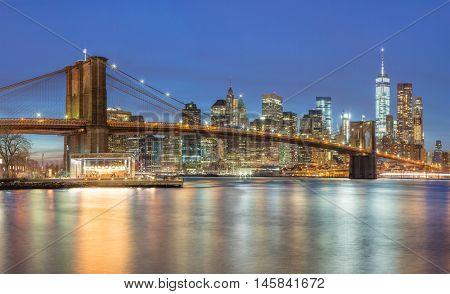 Panoramic view of  Brooklyn Bridge and Lower Manhattan skyline in New York City at night with city illumination, USA
