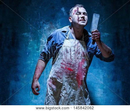Bloody Halloween theme: crazy killer as bloody butcher with a knife on dark blue background