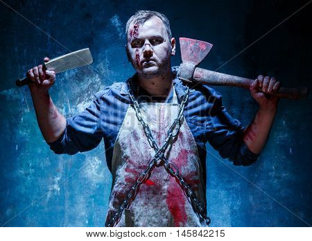 Bloody Halloween theme: crazy killer as bloody butcher with an ax and a knife on dark blue background