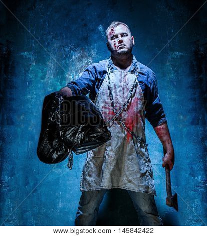 Bloody Halloween theme: crazy killer as bloody butcher with an ax on dark blue background