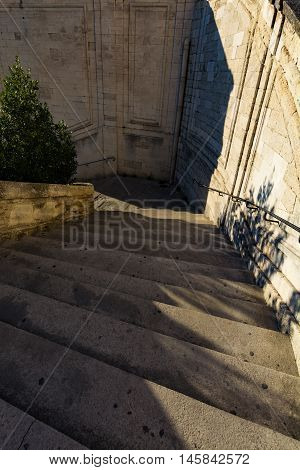 Stairs to the walls of the fortress near the Pope palace with shadowa