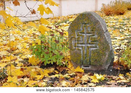 Ancient stone unknown tombstone with a relief cross on a background of yellow maple leaves.