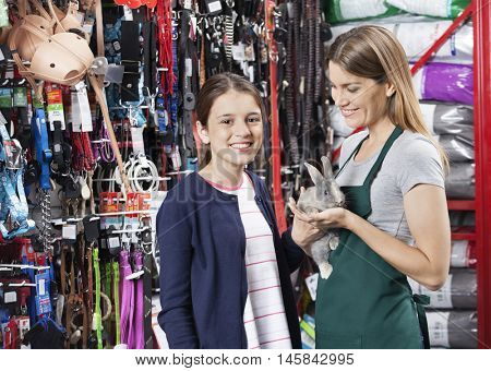 Happy Girl Standing With Saleswoman Holding Rabbit At Store