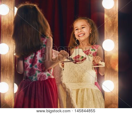 Cute little fashionista. Happy child girl try on outfits looking at mirror.