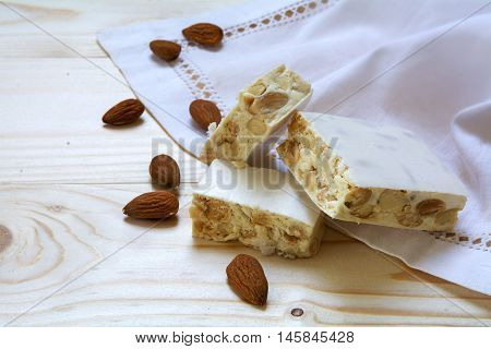 Italian festive torrone or white nougat with almonds and napkin on a wooden table copy space selected focus and narrow depth of field