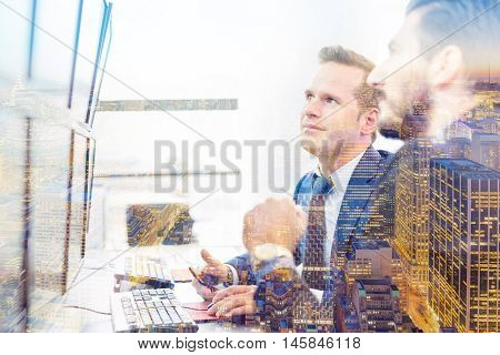 Successful businessmen trading stocks. Equity traders looking at on multiple computer screens in conteporary office. New Your city lights reflection in window. Business success concept.