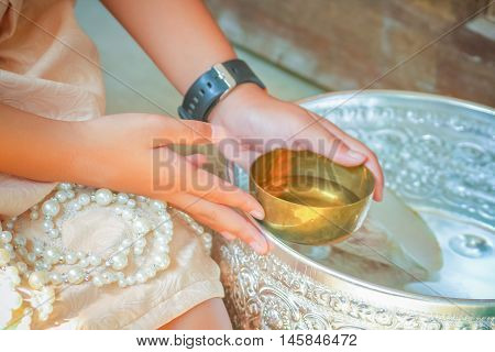 Hand Of A Young Woman Holding Water Bowl In Wedding Ceremony Thai Style.