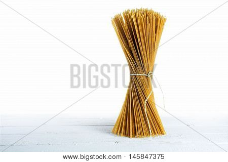 bunch of standing wholemeal spaghetti on white wood high key shot isolated against a white background with generous copy space