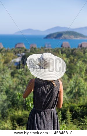 woman in a dress is traveling on the precipice of the mountain in a white hat Vietnam
