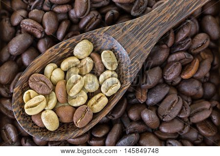 Spoon of dried raw unroasted green coffee berry seeds on top of roasted coffee beans