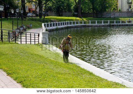 Kaliningrad Russia - August 3 2016: The worker of a garden cuts off a grass near the pond in Kalinigrad