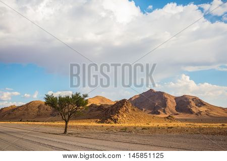 The dirt road in the hills of Namib-Naukluft National Park. Ecotourism in Africa. Travel to Namibia, April
