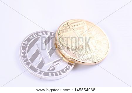 Golden-plated Bitcoin and Silver-plated Litecoin on a white background.