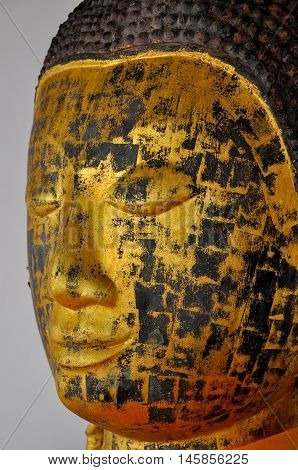 Face of Buddha image after peeling off gold leaves.