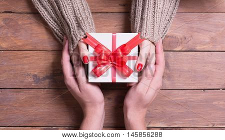 Woman with man holding a christmas gift in hand on wooden background