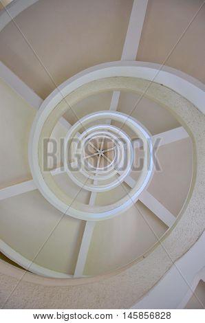Under white spiral stairway, view from bottom up