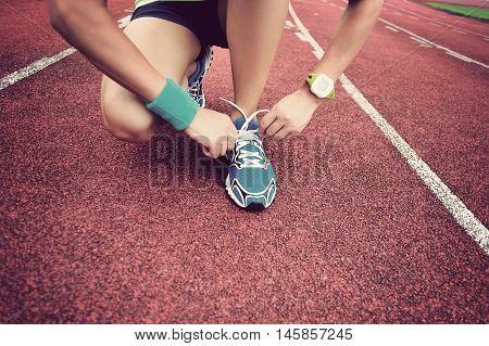 young woman runner tying shoelaces on tracks