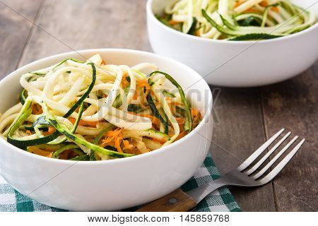 Carrot and zucchini noodles in white bowl on a rustic wooden table