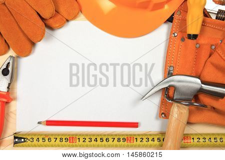 Hard hat, hammer, pliers, nails, red pencil, work gloves and other tools isolated on a wooden background with a white sheet of paper for text