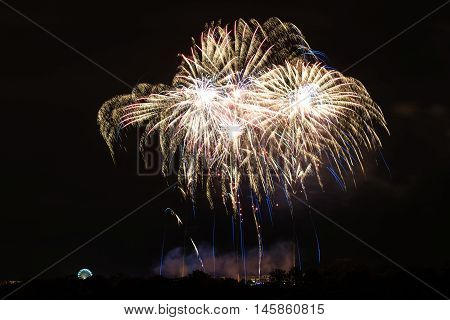 Bright fireworks with ferries wheel to the left - celebrating New Year or other festivities - abstract holiday background