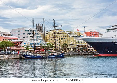 HAMILTON BERMUDA MAY 25 - A tall ship and a cruise ship docked with colorful buildings along Front St. on May 25 2016 in HamiltonBermuda.