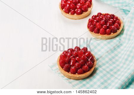 Tartlets with custard, fresh glazed raspberries, served on white wooden table and blue checkered napkin.