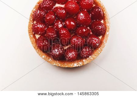 Tartlet with custard, fresh glazed raspberries, served on bright surface. Top view.