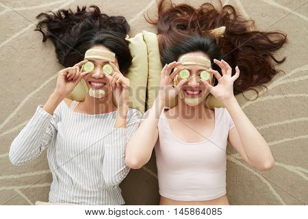 Two young women with cucumber masks lying on the floor
