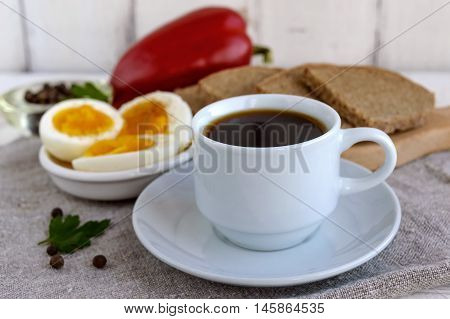 A cup of strong coffee (espresso) close-up and easy diet breakfast - boiled egg and rye bread - in the background.