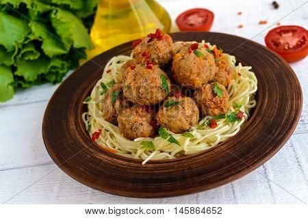 Pasta (spaghetti) with meat balls in a clay bowl on a dark background.