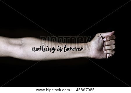 closeup of a young Caucasian man with the text nothing is forever simulating a tattoo in his forearm, against a black background