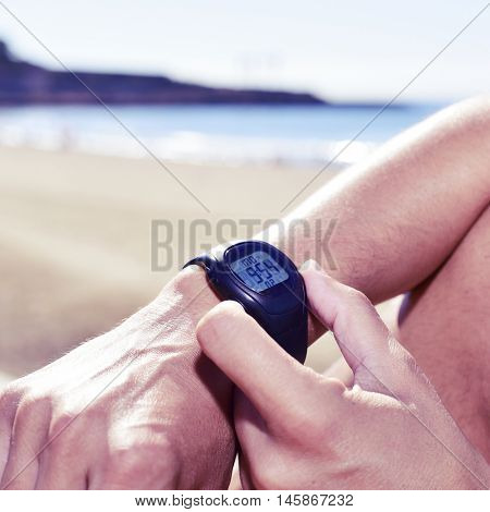 closeup of a young sportsman syncing his smartwatch, with the sea in the background