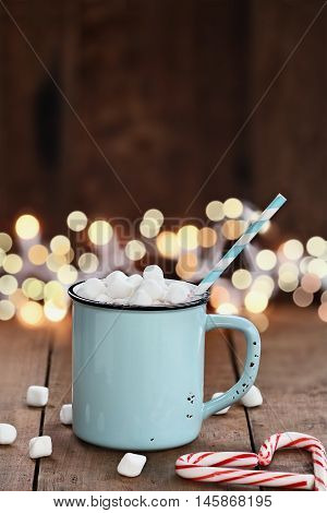 Enamel cup of hot cocoa with mini marshmallows and candy canes in the shape of a heart against a rustic background with beautiful Christmas lights of bokeh. Could also be coffee. Perfect winter time treat.
