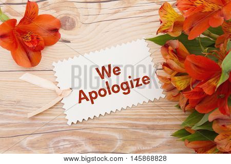We Apologize Message Some lilies on weathered wood with We Apologize Gift Card and copy space for your message