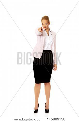 Angry business woman pointing at camera