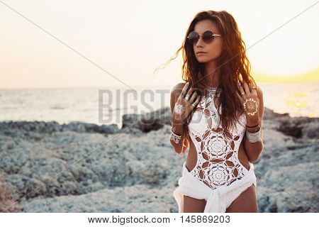poster of Beautiful boho styled girl wearing white crochet swimsuit with flash tattoo at the beach in sunlight