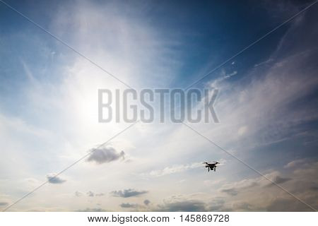 Done quad copter flying hovering in the blue sky, silhouette