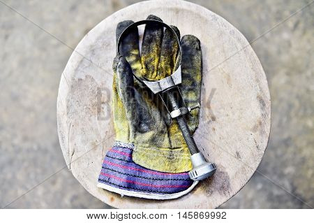 Dirty worker's glove holding a oil filter key on a wooden plank in a workshop