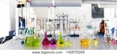 Laboratory table piled tubes with colored liquid colored reagents in flasks and test tubes