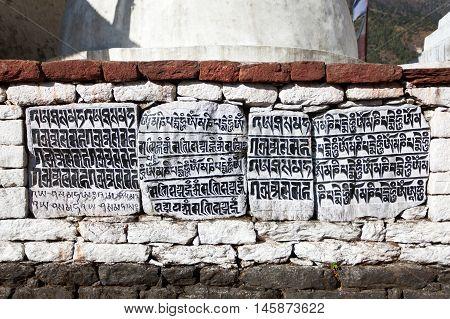 buddhist mani prayer wall on the way to Everest base camp with buddhist tibetan symbols and prayer flags Khumbu valley Sagarmatha national park Nepal