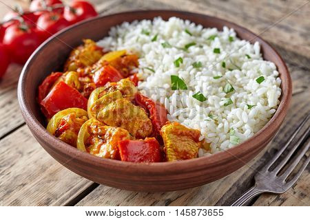 Chicken jalfrezi healthy traditional Indian curry spicy fried meat with vegetables and basmati rice food in clay plate on vintage table background