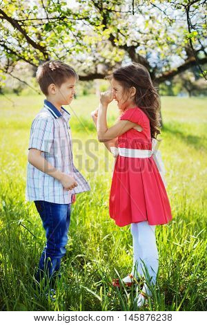 little girl quarrels with a young boy in the garden