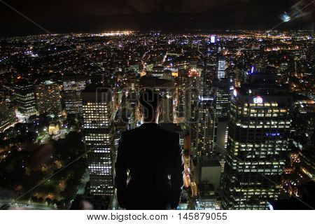 Business man on rooftop looking at illuminated night city. Research concept