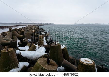 Many breakwaters with snow on the northern mall in the town of Baltiysk, Kaliningrad, Russia.