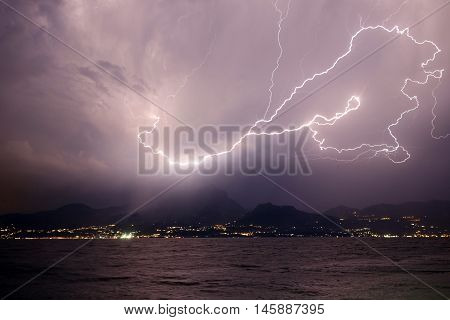 Lightning over the mountains at lake garda in Italy