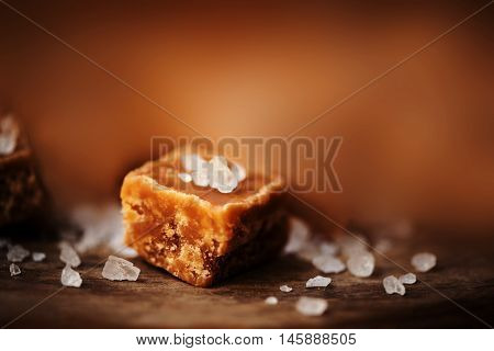 Caramel candies on brown background. Salted caramel pieces