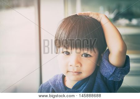 Asian boy is touching his head and hair thinking.