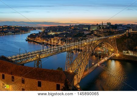 Dom Luis I Bridge in Porto on sunset background.