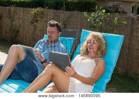 Happy Couple Resting In Deck Chairs By Pool With Tablet